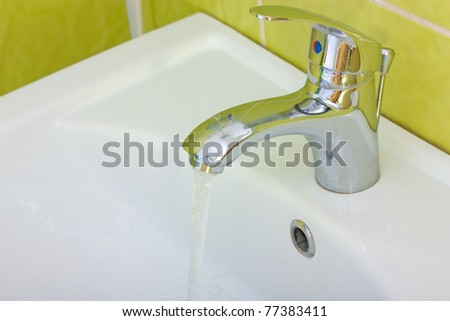 A chrome  bathroom sink with water tap - stock photo