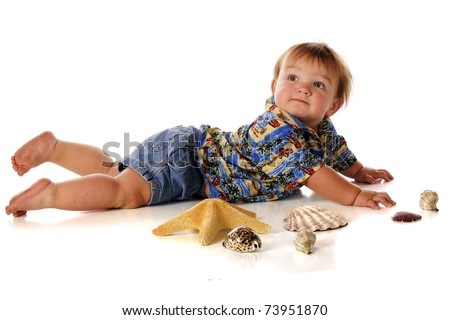A chubby baby boy looking up over his shoulder as he lays in his surfing shirt and shorts among sea shells and a star fish.  Isolated on white.