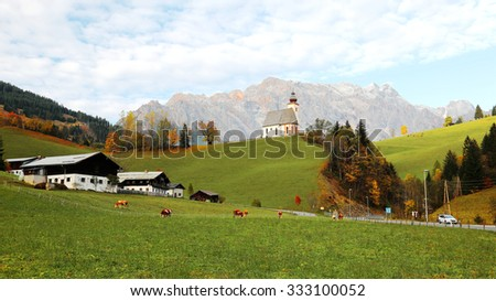 A church high on hilltop with a mountain range in the background and a grassy ranch in the foreground ~ Beautiful scenery of St. Nikolaus Church of Dienten Village and Hochkoenig Mountains in Austria - stock photo