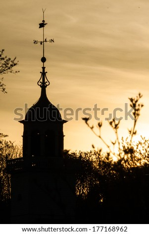 A church steeple with a weather vane silhouetted against a sunset.  Mission Church, Mackinac Island, MI, USA. - stock photo