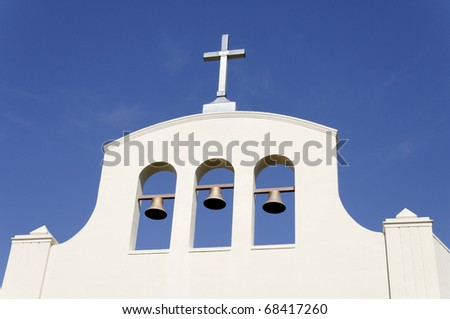 A church with a cross and three bells against a clear blue sky.