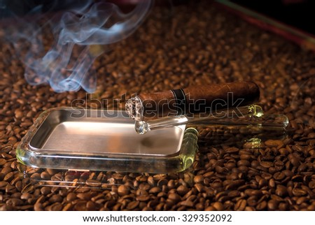a cigar in an ashtray and a cloud of smoke - stock photo