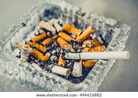 A cigarette burning in an glass ashtray full of butts. - stock photo