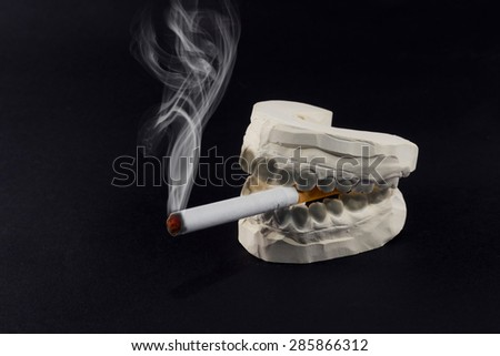 A cigarette in his mouth that harms the health of our teeth