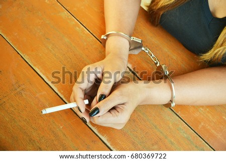 A cigarette in the hands of a cuffed female suspect during the investigation