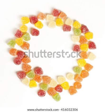 A circle formed by many vibrant gumdrops, shot from above on white background, with copyspace - stock photo