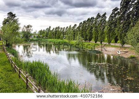 A city park with pond under heavy wind and stormy sky. - stock photo