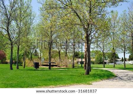 A city park with trees and a picnic table - stock photo