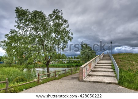 A city park with under heavy wind and stormy sky. - stock photo