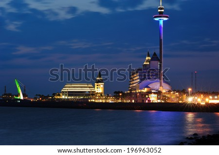 A city with a large building brightly lit at night. - stock photo