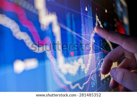 A city worker Analysing stock market data on a monitor.