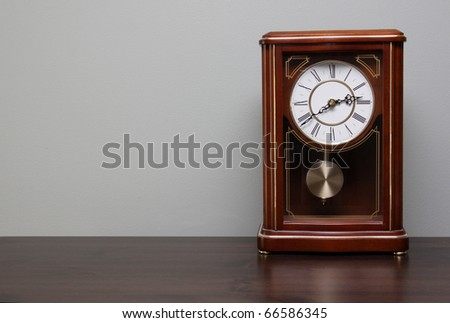 A classic analog clock sitting a table with copy-space. - stock photo