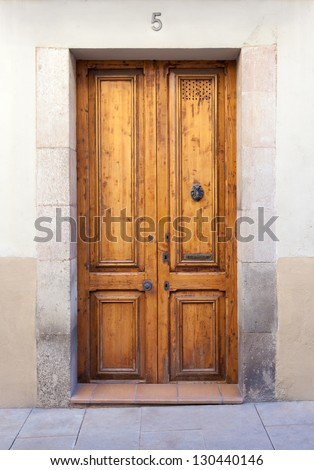 "A classic double wooden door with a knocker and a mail slot (labeled ""cartes"", which means ""letters""). Shot in the Sarri�  quarter of Barcelona, where old wooden doors are typical. - stock photo"