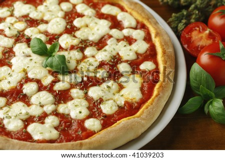 A classic italian pizza margherita with tomatoes souce, mozzarella and basil on a table. - stock photo
