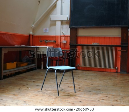 A classic school chair in the middle of an empty classroom with desks and black-board - stock photo