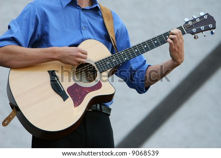 A classic six string guitar being played by a young man - stock photo