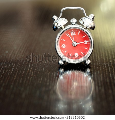 A Classic Style Clock on Wooden Table - stock photo