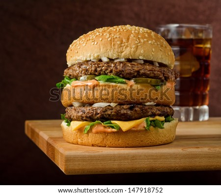 A classic style double cheeseburger with two beef patties, sauce, lettuce, cheese, pickles, and onions on a sesame seed bun with soda. - stock photo