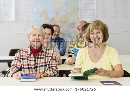 A classroom full of mature students with books. - stock photo