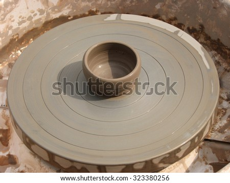 A clay pot on a pottery wheel, pottery craft - stock photo