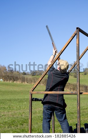 A clay shooter in the stand aiming at the clay pigeon target - stock photo