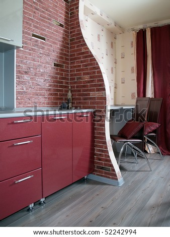 A clean modern red kitchen with a brick wall - stock photo