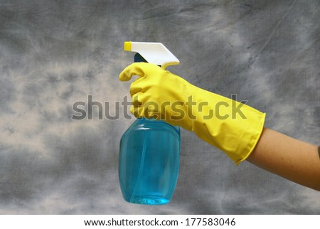 A cleaning person prepares to clean using a spray bottle. - stock photo