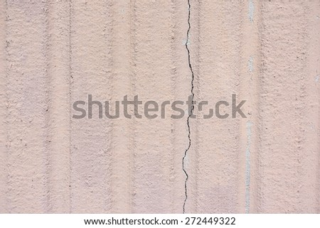 A clear view of an exterior grooved beige wall with crack. - stock photo