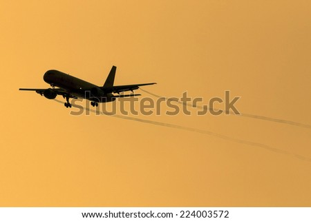 A 757 cleared for landing trailing vapor trails - stock photo