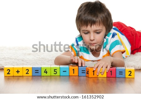 A clever boy is playing with blocks on the floor