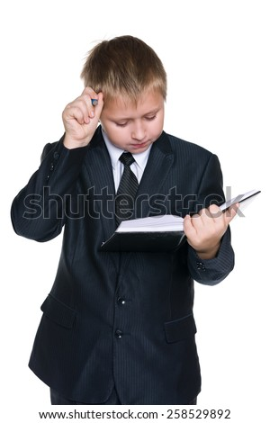 A clever young boy with a notebook on the white background - stock photo