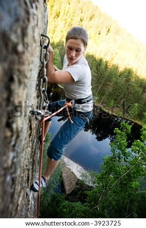 A climber at the top of a ledge looking down with fear. - stock photo