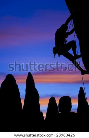 A climber clings to the side of an overhanging rock in The Sierra Nevada Mountains, California. - stock photo