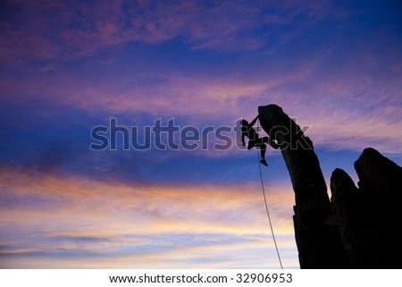 A climber dangles from the edge of an overhanging rock in The Sierra Nevada Mountains, California. - stock photo
