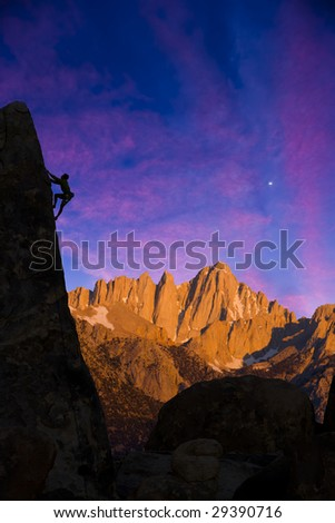 A climber is silhouetted against the evening sky as he clings to a steep rock face in the Sierra Nevada Mountains, California. - stock photo