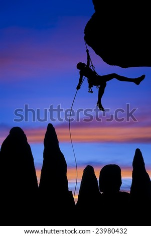 A climber is silhouetted as she  dangles in midair rappelling from the summit of a rock spire in The Sierra Nevada Mountains, California. - stock photo