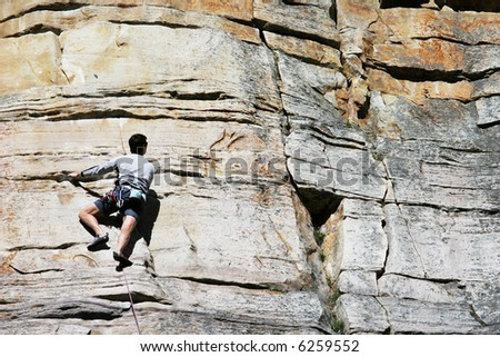 A Climber slowly moves upwards along a vertical wall - stock photo