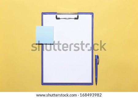 a clipboard on a yellow background and a blue pen - stock photo
