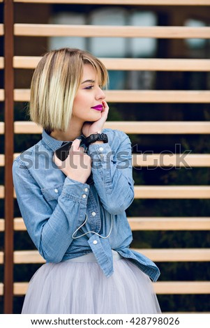 A close portrait of a dreamy girl with pink lips and blond hair looking to her left listening to music on a smartphone with striped wooden balks behind wearing blue jeans shirt and grey tulle skirt