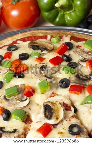 A close-up cropped image of supreme pizza on a stainless pan - stock photo