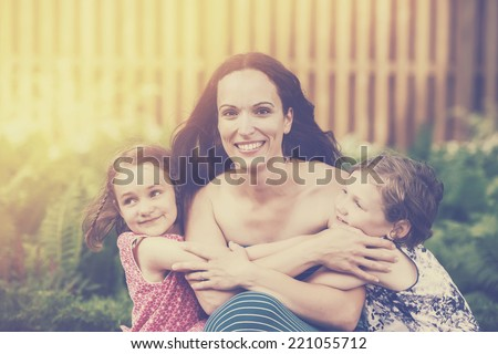 A close up family picture of two daughters on either side of their mother giving her a hug.  Filtered for a retro, vintage look.  - stock photo