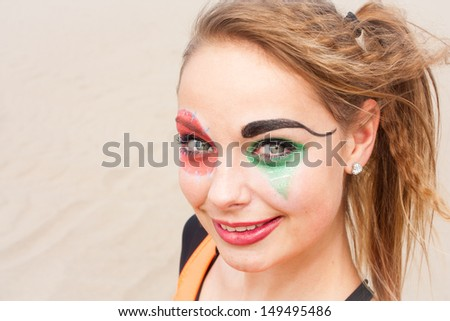 A close-up head shot of a young female circus performer with clown make-up smiling and looking up into the camera.
