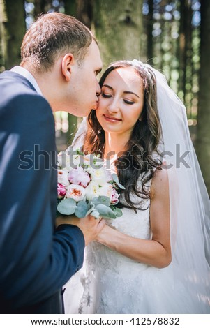 A close up image of a beautiful wedding couple kiss. Concept of love and family. - stock photo
