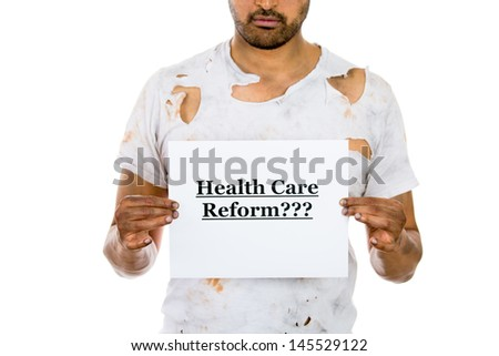 A close-up image of a homeless man who lost his job holding a sign health care reform, isolated on a white background. universal health care coverage. Politics. Legislation in healthcare. - stock photo