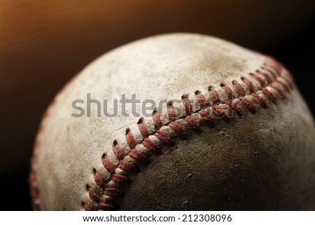 A close-up image of a worn baseball with an out of focus bat in the background - stock photo