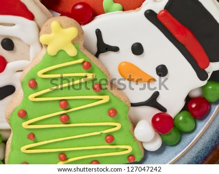 A close-up image of assorted cookies focusing the Christmas tree shape on the plate - stock photo