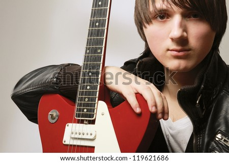 A close-up image of male with guitar - on grey background - stock photo