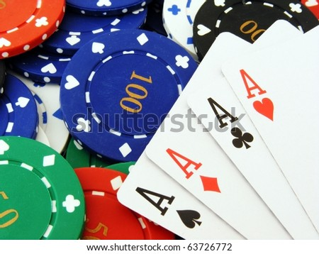 A close up macro image of 4 aces lying on a stack of poker chips - stock photo