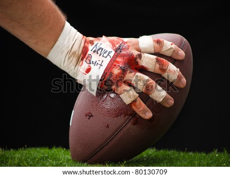 A close up of a beat up hand about to hike a football. - stock photo