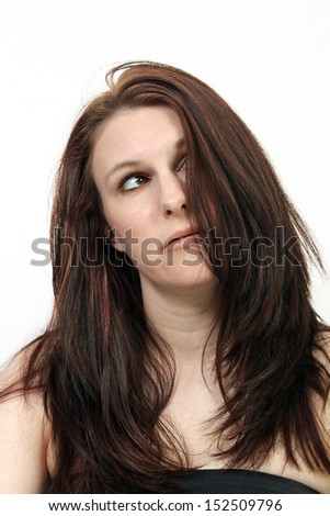 A close-up of a beautiful young brunette who appears to be tired, frustrated, or frazzled. - stock photo